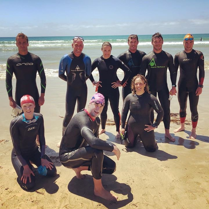 image is of a number of club members in their wetsuit standing in front of the water on the beach